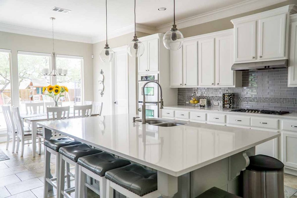 a modern kitchen with white cabinetry and white countertops