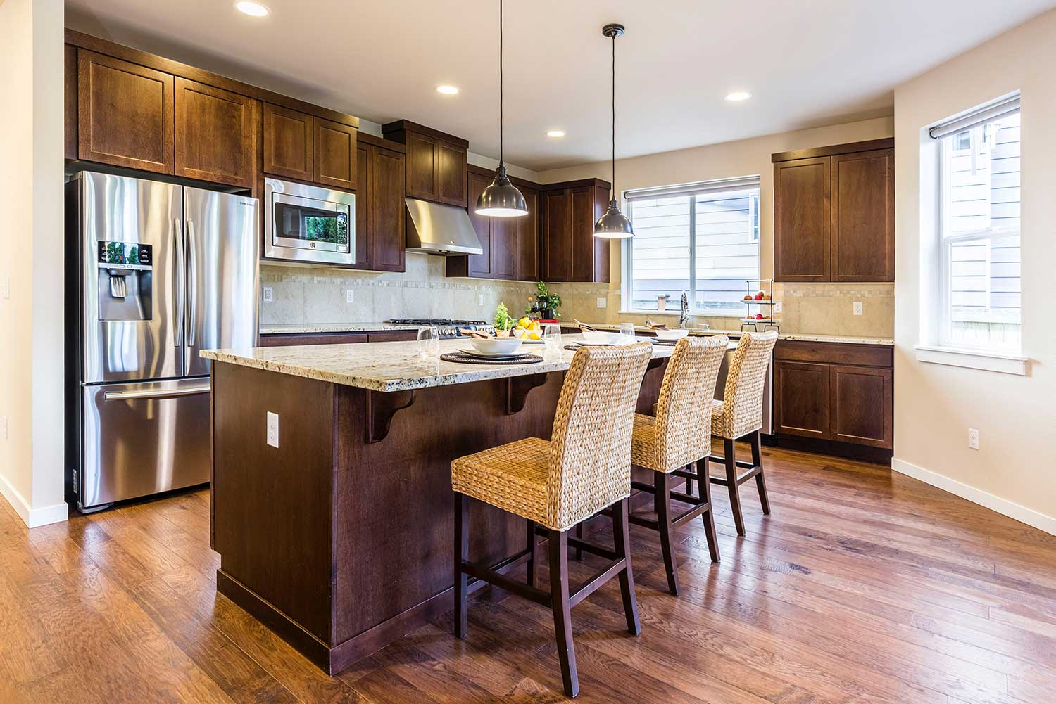 a modern kitchen with dark cabinetry and stone countertops