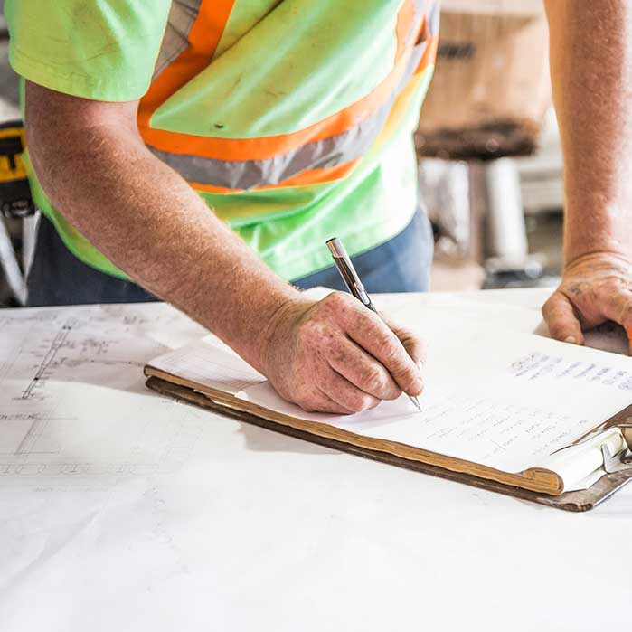 a construction worker marks notes on a notepad