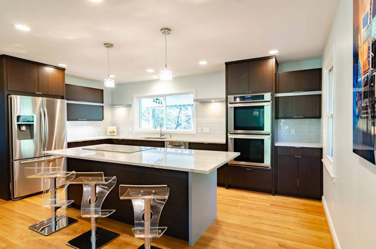 a modern kitchen with dark cabinetry and white countertops