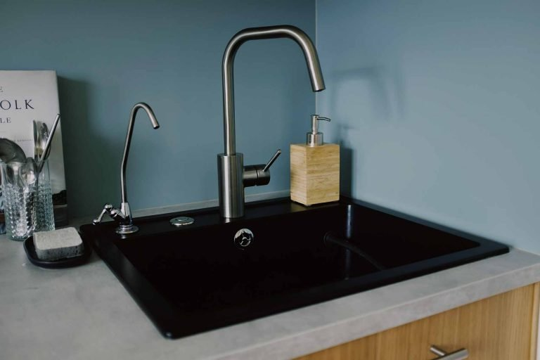 A kitchen sink with a modern faucet