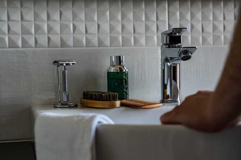 A bathroom sink with shaving products and a man's hand